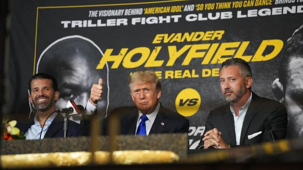 Former President Donald Trump, center, gives a thumbs-up to cheering supporters as he and his son Donald Trump Jr., left, prepare to provide commentary for a boxing event headlined by a bout between former heavyweight champ Evander Holyfield and former MMA star Vitor Belfort, Saturday, Sept. 11, 2021, in Hollywood, Fla. (AP Photo/Rebecca Blackwell)