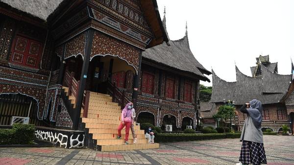 Pengunjung berfoto di area anjungan Sumatera Barat di TMII, Jakarta, Minggu (12/9/2021).