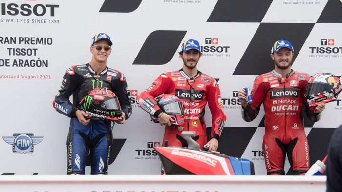 ALCANIZ, SPAIN - SEPTEMBER 11: (L-R) Fabio Quartararo of France and Monster Energy Yamaha MotoGP Team, Francesco Bagnaia of Italy and Ducati Lenovo Team and Jack Miller of Australia and Ducati Lenovo Team pose at the end of the MotoGP qualifying practice during the MotoGP of Aragon - Qualifying  at Motorland Aragon Circuit on September 11, 2021 in Alcaniz, Spain. (Photo by Mirco Lazzari gp/Getty Images)