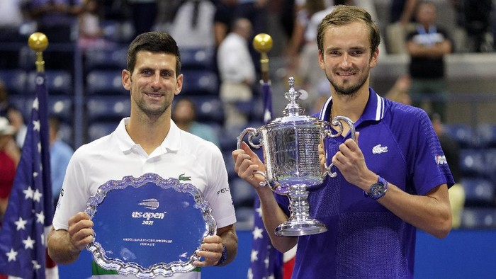 Daniil Medvedev, of Russia, right, and Novak Djokovic, of Serbia, pose for photos after Medvedev defeated Djokovic in the mens singles final of the US Open tennis championships, Sunday, Sept. 12, 2021, in New York. (AP Photo/John Minchillo)