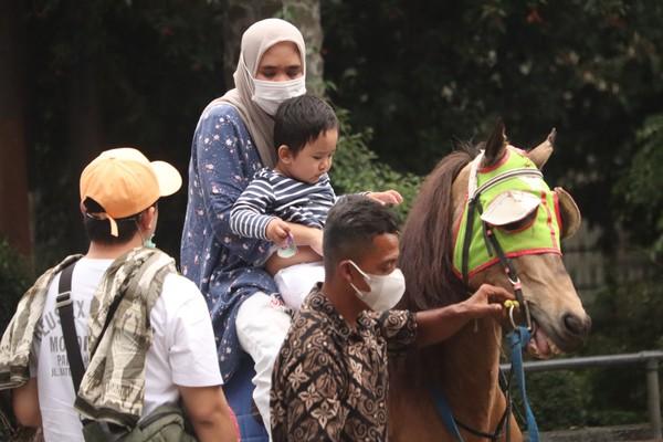 Ada juga, wisatawan yang memilih mengejak anaknya naik kuda di Jalan Ganesha tepatnya didepan Gerbang kampus ITB Bandung.Foto: Wisma Putra/detikcom