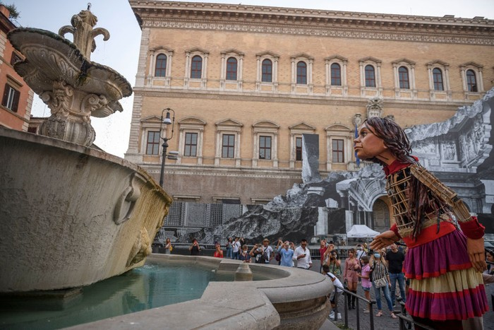 ROME, ITALY - SEPTEMBER 12: People greet Little Amal, a giant puppet depicting a young Syrian refugee girl, as she walks in the city, on September 12, 2021 in Rome, Italy. Little Amal is a 3.5 meter puppet walking 8,000 kilometers across Europe to highlight the plight of child refugees. There are some 26 million refugees worldwide, and more than half of them are children. (Photo by Antonio Masiello/Getty Images)