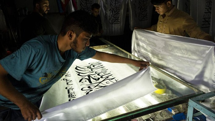 American and Taliban flags are seen in flag printing workshop in Kabul's Jawid market, Afghanistan, Sunday, Sept. 12, 2021. The small flag shop, tucked away in the courtyard of a Kabul market, has documented Afghanistan's turbulent history over the decades with its ever-changing merchandise. Now the shop is filled with white Taliban flags, emblazoned with the Quran's Muslim statement of faith, in black Arabic lettering. (AP Photo/Bernat Armangue)