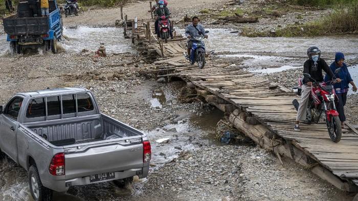 Sejumlah warga membantu mendorong sebuah mobil yang tidak bisa melewati jembatan darurat di Desa Jono Oge, Sigi Sulawesi Tengah, Senin (13/9/2021). Jalan yang menghubungkan sejumlah kecamatan di Kabupaten Sigi itu terendam air sungai yang meluap sejak sepekan lalu dan hingga kini belum mendapat penanganan dari instansi terkait sehingga masyarakat setempat berinisiatif membuat jembatan darurat secara swadaya agar dapat dilintasi. ANTARA FOTO/Basri Marzuki/hp.