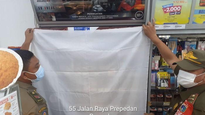 Satpol PP Jakarta Barat tutupi produk rokok di minimarket.