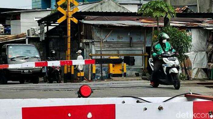 Seorang driver ojek online (ojol) nekat terobos palang pintu Kereta Api (KA) yang sudah tertutup di perlintasan, Jalan Pangadegan Selatan, Jakarta, Rabu (15/09/2021).