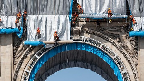 Para pekerja memulai proses membungkus monumen Arc De Triomphe dengan kain perak di Paris, Prancis.
