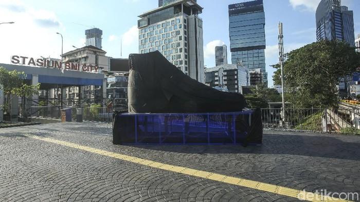 Sebuah kain hitam menutupi benda berbentuk sepatu besar di Kawasan Sudirman, Jakarta, Rabu (15/9/2021). Penasaran?