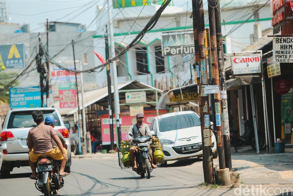 Sejumlah tiang yang berdiri di badang jalan WR Supratman, Ciputat Timur, Tangerang Selatan, masih berdiri tegak, Jumat (17/9/2021). Belasan tiang masih berdiri memakan badan jalan di Ciputat Timur. Padahal, tiang-tiang utilitas itu harus sudah dipindahkan sebelum 20 September 2021.