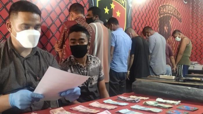 Petugas memperlihatkan barang bukti dan tersangka perjudian yang ditangkap di Kecamatan Kuala Batee, Kabupaten Aceh Barat Daya, Jumat (ANTARA/Suprian)