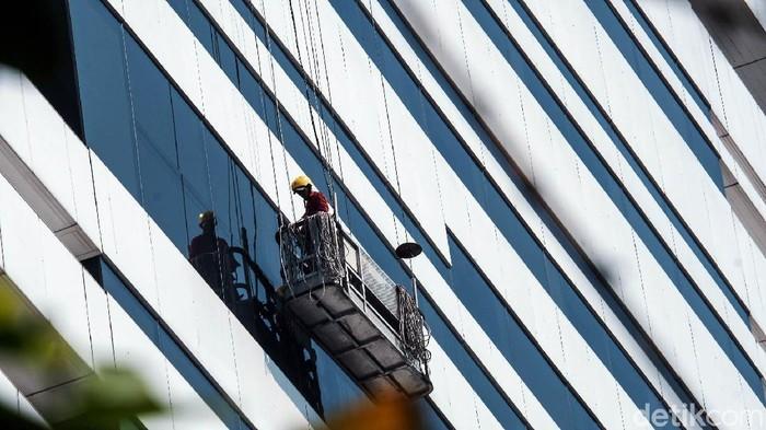 Sejumlah petugas membersihkan kaca gedung bertingkat di ibu kota pagi ini. Peralatan yang digunakan haruslah standar demi keselamatan bekerja.