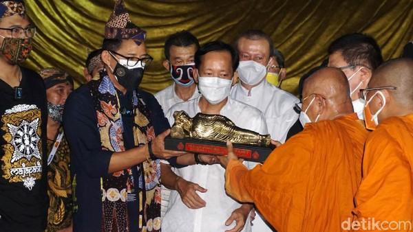 Bante Mahaviara Majapahit memberikan cendera mata patung Budha tidur ke Sandiaga Uno.