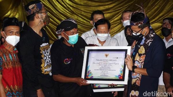 Sandiaga menyerahkan piagam penghargaan Desa Wisata Kampung Majapahit Bejijong yang masuk 50 besar desa wisata terbaik di Indonesia. Di depan patung Budha tidur terbesar ketiga di Asia Tenggara, ia juga menandatangani prasati penetapan Bejijong sebagai Desa Wisata Kampung Majapahit.