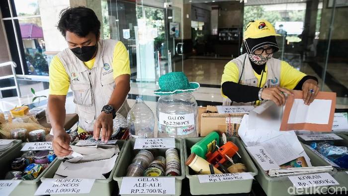 Pekerja tengah menunjukan sampah-sampah yang telah dipilah dan bisa ditukar dengan uang saat berlangsungnya acara World Clean Up Day di Jakarta Selatan, Sabtu (18/9/2021). Bank Sampah Budi Luhur yang sudah berdiri sejak 2017 ini menerima berbagai macam sampah dari masyarakat untuk kemudian ditukarkan dengan sejumlah rupiah.