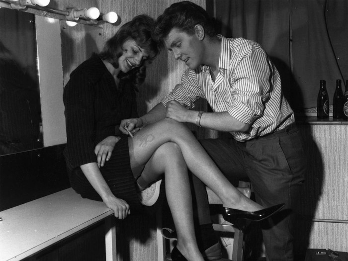 September 1962:  English pop singer Shane Fenton, later known as Alvin Stardust, autographing a womans leg in his dressing room.  (Photo by John Pratt/Keystone Features/Getty Images)
