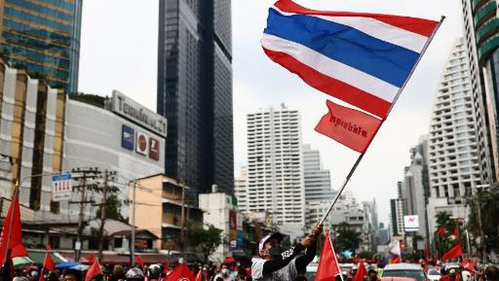 An anti-government protester waves a national flag as they gather for a demonstration to mark the 15-year anniversary of the 2006 military takeover in Bangkok on September 19, 2021, and urge the resignation of the current administration over its handling of the Covid-19 coronavirus crisis. (Photo by Jack TAYLOR / AFP)