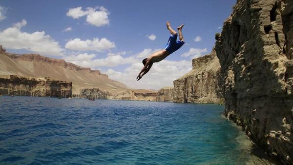 Kalau traveler yang jago berenang, silakan mencoba lompat dari atas tebing seperti ini. Sensasinya pasti ngeri-ngeri sedap! (Xinhua/Latif Azimi)