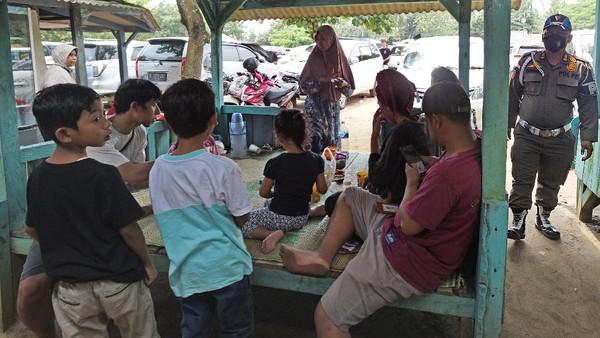 Guna mencegah terjadinya kerumuman serta memantau penerapan protokol kesehatan di area objek wisata, sejumlah personel Satuan Polisi Pamong Praja pun dikerahkan untuk mengawasi pengunjung di Pantai Sembolo. (ANTARA FOTO/Asep Fathulrahman)