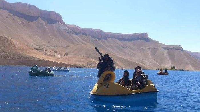 Petempur Taliban naik perahu bebek sambil menenteng senjata (Twitter/@Jake_Hanrahan)