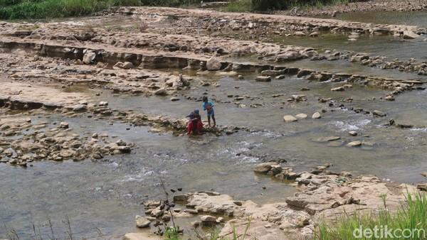 Melongok ke arah sungai, tampak orang-orang yang didominasi keluarga tengah berada di pinggir sungai. Sementara, tampak beberapa mobil terparkir di pinggir jalan tersebut. (Pradito Rida Pertana/detikTravel)