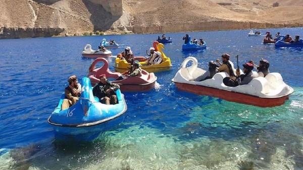 Tentara Taliban menikmati kesempatan berwisata di sebuah danau berair biru yang cantik. Mereka terlihat asyik mengayuh mainan bebek-bebekan di atas air danau, namun tetap dengan menenteng senjata laras panjang. (Twitter)