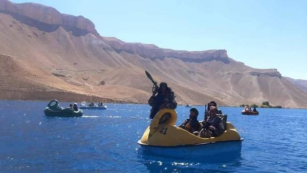 Bahkan ada juga yang memegang peluncur rudal. Tampang mereka yang garang, berbanding terbalik dengan bebek-bebekan warna-warni yang mereka naiki. Lokasi wisata tempat mereka main bebek-bebekan ini disebutkan di danau Band-e Amir. (Twitter)