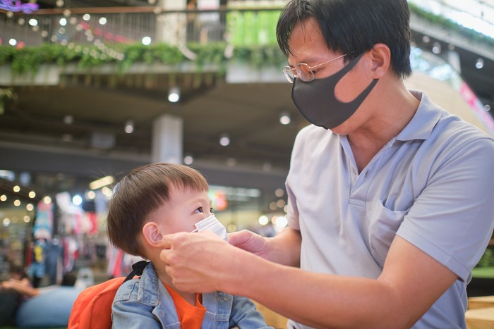 Parent putting mask on his Asian toddler boy child, Dad and son wearing protective medical mask in public area, shopping center, Concept of coronavirus quarantines and Air pollution pm2.5 in Thailand