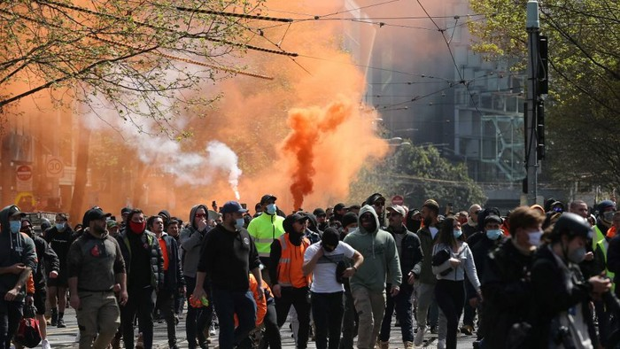 Flares are lit as construction workers and demonstrators attend a protest against Covid-19 regulations in Melbourne on September 21, 2021. (Photo by CON CHRONIS / AFP)
