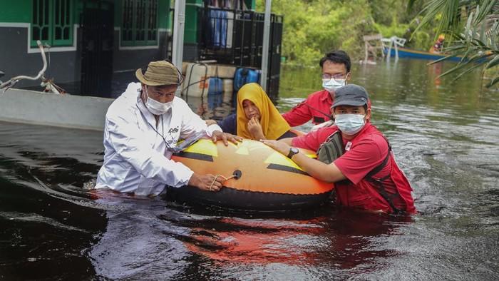 Petugas gabungan mengevakuasi warga terdampak banjir di Jalan Danau Ranggas, Palangkaraya, Kalimantan Tengah, Selasa (21/9/2021). Sebanyak 45 warga terdampak banjir luapan Sungai Kahayan dan Sungai Rungan dievakuasi guna mendapatkan perawatan kesehatan di RS Kota Palangkaraya dan posko pengungsian, karena banjir yang semakin tinggi merendam permukiman warga dalam seminggu terakhir. ANTARA FOTO/Makna Zaezar/aww.