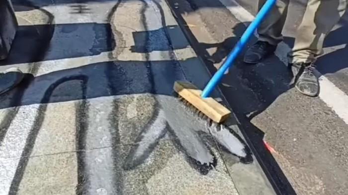 Petugas membersihkan gambar alien di pedestrian Dago