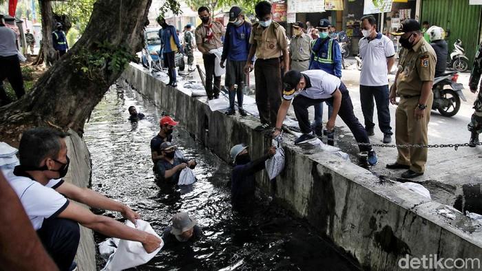 Antisipasi banjir saat musim hujan terus dilakukan di Jakarta. Kali ini, tim gabungan TNI AL Lantamal 3 dan Pemkot Jakarta Utara membersihkan saluran air di kawasan Ancol.