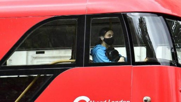 A passenger wears a face-mask as a Covid-19 protective measure as she travels on a bus in central London on July14, 2021. - London Mayor Sadiq Khan on Wednesday called for use of face coverings to remain compulsory on public transport in the British capital after government plans to relax Covid curbs begin on July 19. (Photo by JUSTIN TALLIS / AFP)