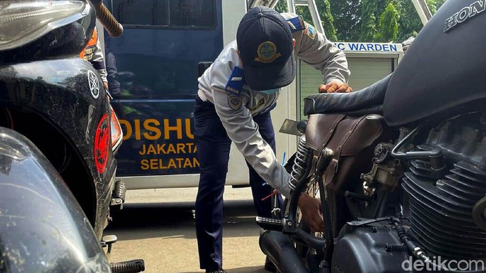 Dishub DKI Jakarta menggelar razia parkir liar di kawasan Kalibata, Jakarta. Sejumlah motor yang kedapatan parkir sembarangan dikempiskan bannya.