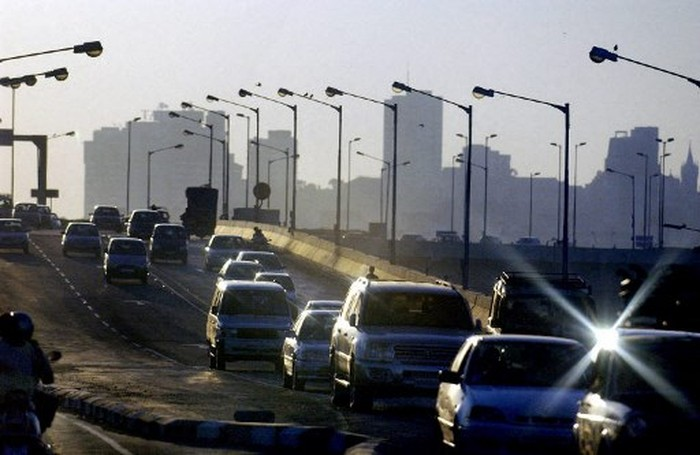 A picture taken 14 January 2004 shows traffic on an overpass advances on one of the newer bridges build in the commercial capital, with the skyline of Bombay in the background.  Union Finance Minister, Palaniappa Chidambaram during his Union Budget televised address 08 July 2004, announced there will be more impetus to growth in the infrastructure and road sectors. (Photo by ROB ELLIOTT / AFP)