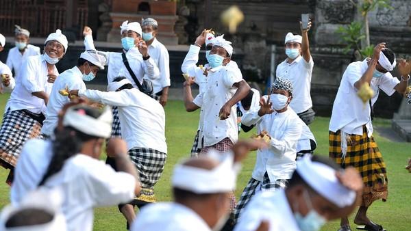 Sejumlah warga melempar ketupat ke arah warga lainnya saat tradisi Perang Ketupat di Desa Kapal, Badung, Bali, Selasa (21/9/2021).