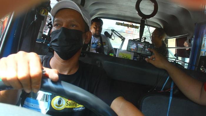 Sebuah angkutan kota di Malang disulap jadi studio podcast keliling. Studio itu dioperasikan untuk promosikan keunikan kawasan wisata setempat. Ini fotonya.