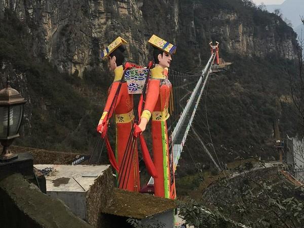 Menara Jembatan Kaca Gunung Jiuhuangshan di Mianyang, Sinchuan juga masuk dalam nominasi. Di sana terdapat dua patung besar pria dan wanita yang mengenakan pakaian tradisional. (Archy.com)