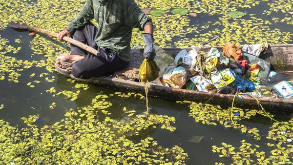 Untuk mendayung di atas danaunya pun kini sulit. Seorang tukang perahu menekan keras dayungnya untuk bisa melewati limbah. (Mukhtar Khan/AP)