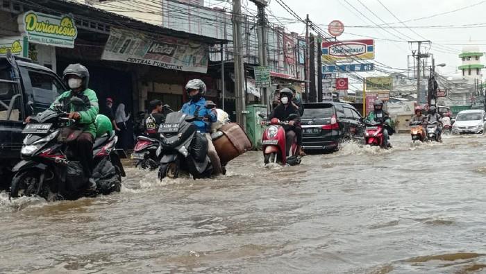 Jalan Raya Sawangan tergenang air setinggi 30 Cm, lalu lintas macet. Pengendara motor ada yang mogok.