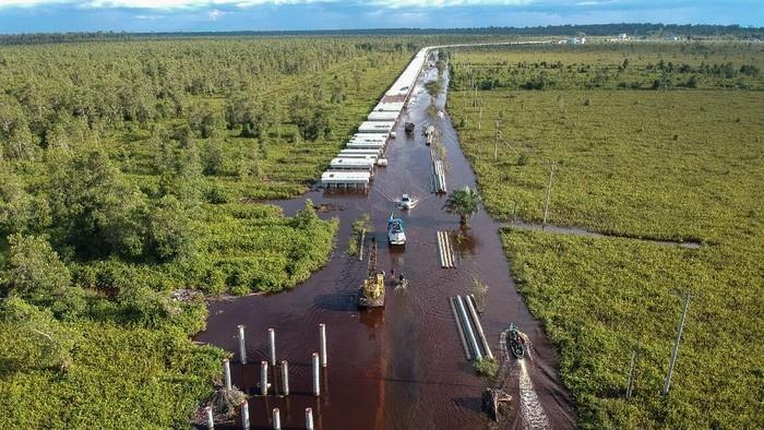 Foto udara pengendara mobil berusaha menerobos banjir yang merendam di jalan trans Kalimantan Bukit Rawi, Pulang Pisau, Kalimantan Tengah, Kamis (23/9/2021). Banjir luapan Sungai Kahayan dan Sungai Rungan kiriman dari wilayah hulu tersebut masih merendam sepanjang 2,5 kilometer jalan nasional Kalimantan Bukit Rawi sejak Senin (30/8/2021) dan akibatnya akses jalan tidak bisa dilalui kendaraan bermotor. ANTARA FOTO/Makna Zaezar/foc.