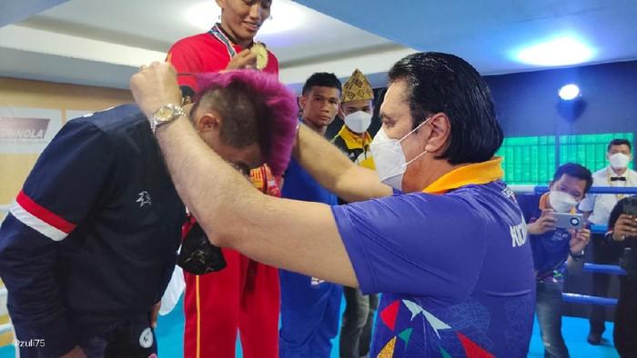 Bendahara Umum PP KBI, Karan Sukarno Walia, sedang mengalungkan medali kepada juara eksebisi Kickboxing PON XX Papua.