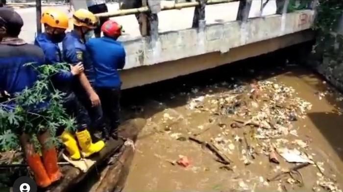 Petugas PUPR Depok membersihkan sampah yang menyumbat Kali Mampang hingga menimbulkan banjir di Sawangan