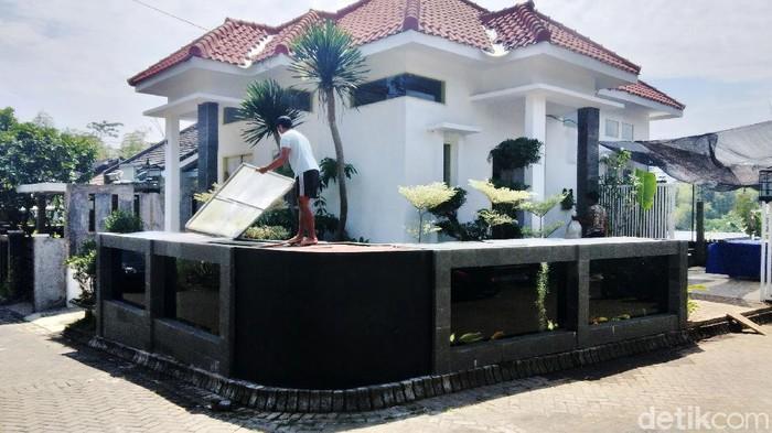 Rumah warga di Perum Tirtasari, Kecamatan Wagir, Kabupaten Malang, sungguh unik. Pagar rumahnya dibuat dari kolam koi.