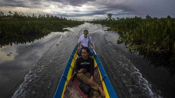 Pengunjung menggunakan kelotok (perahu bermesin) untuk menuju makam Syekh Muhammad Ilyas (Datu Muning) di Desa Sungai Rutas, Kabupaten Tapin, Kalimantan Selatan, Kamis (23/9/2021).
