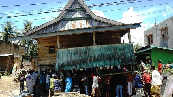 Warga bergotong royong memindahkan rumah panggung di Desa Bunde, Mamuju, Sulawesi Barat, Jumat (24/9/2021).