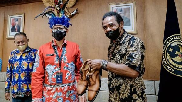 Dalam kesempatan tersebut, Sandiaga juga tampak memberikan hadiah sepatu merk Prabu miliknya kepada Ketua II Dewan Adat Papua Sayid Fadhal Alhamid (kanan) disaksikan Sekretaris Umun Dewan Adat Papua Leonard Imbiri (kiri) saat menerima tokoh masyarakat adat Papua yang merupakan perwakilan dari panitia pelaksana Konferensi Besar Masyarakat Adat Papua IV di Gedung Sapta Pesona, Jakarta.