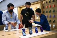 People wait in line to purchase newly released products at the Apple Store in Orchard Road on September 24, 2021 in Singapore. Apple announced September 14 the release of four variants of its latest iPhone 13, alongside other upgrades to its product lineup. (Photo by Feline Lim/Getty Images)