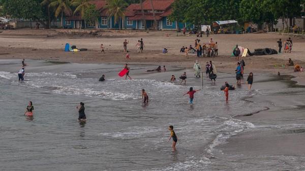 Pengunjung bermain air di Pantai Carita, Pandeglang, Banten, Minggu (26/9/2021). ANTARA FOTO/Muhammad Bagus Khoirunas.