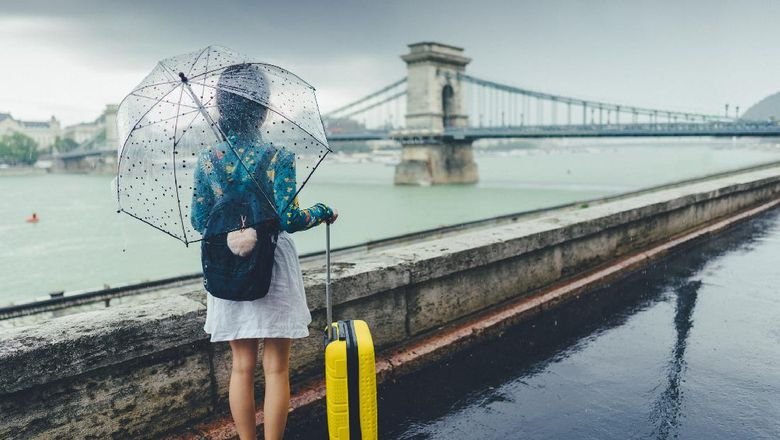 Rear view of young woman with umbrella and suitcase just arriving in Budapest