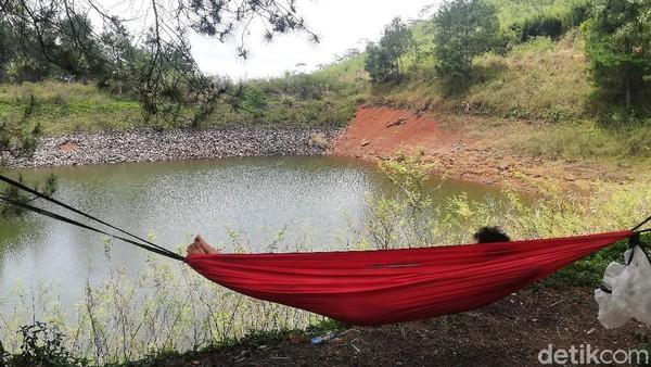 Tampak pengunjung sedang bersantai di atas hammock sambil menikmati keindahan permukaan air Cekdam Cimarias.